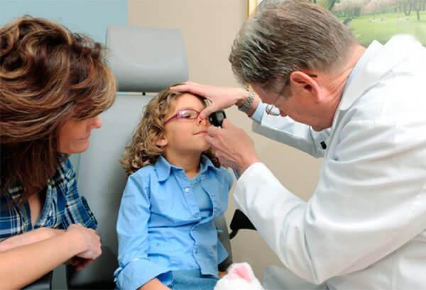 Доктор обследует ребенка с частым кровотечением из носа