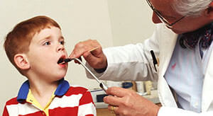 При осмотре горла доктор диагностирует ларингит