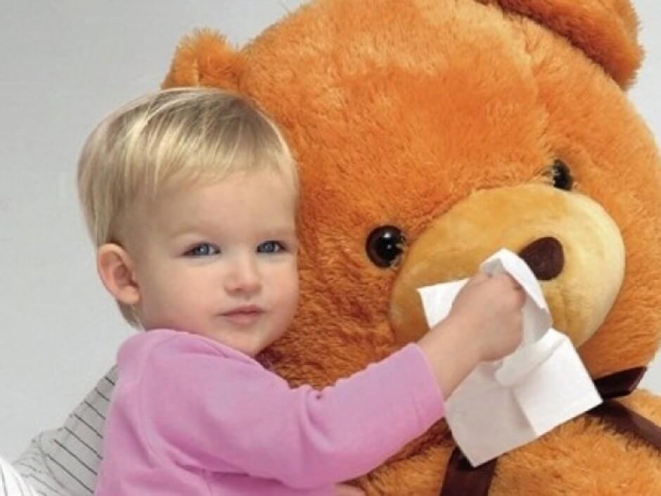 Ребенок вытирает нос медвежонку