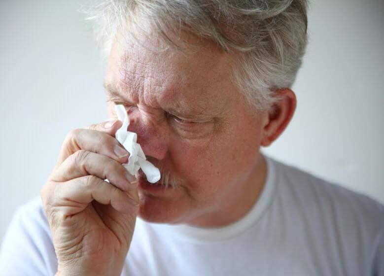 Мужчина вытирает нос
