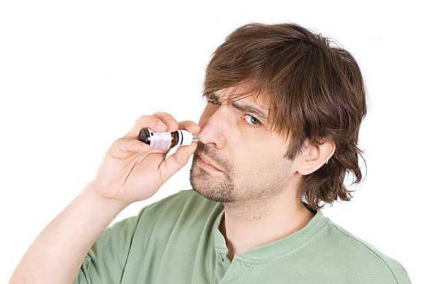 Мужчина закапывает нос